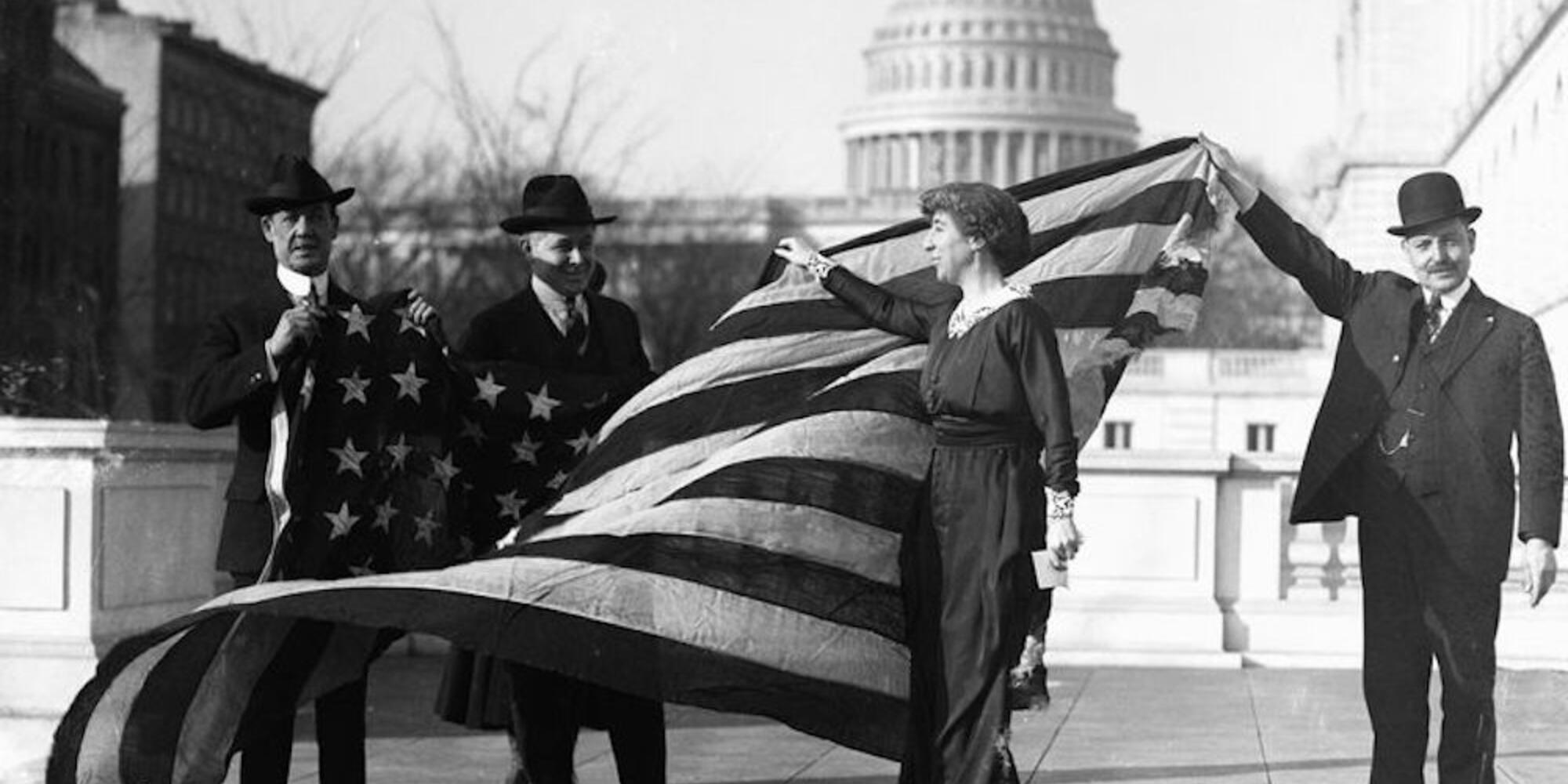 Jeanette Rankin, first Woman elected to Congress, receiving the flag of the House of Representatives upon passage of women's suffrage.